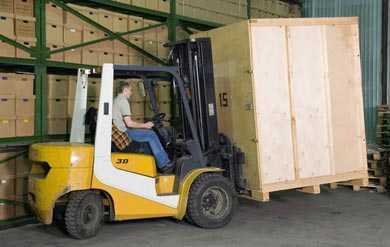 A forklift moving a crate into a shipping truck.
