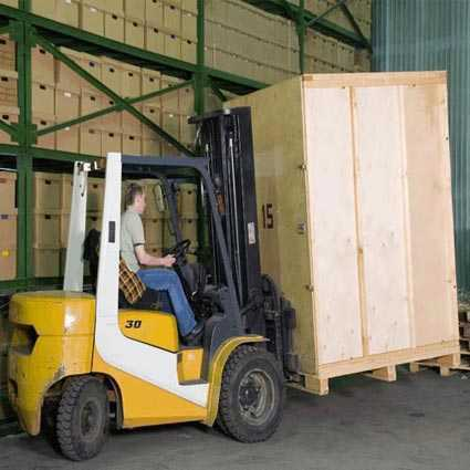 A forklift carefully moving a large crate.